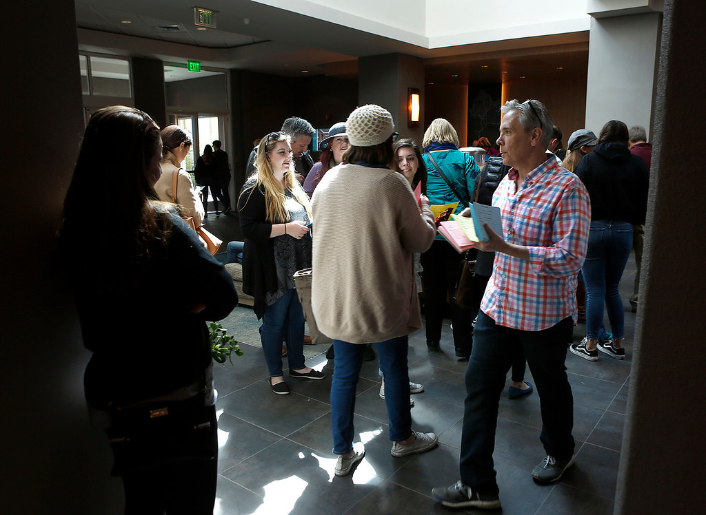 . Casting director Rich King hands out forms to prospective actors in the lobby at Embassy Suites during open casting for HBO\'s Big Little Lies in Seaside on Saturday March 17, 2018. The line of thousands snaked out the door, around the building and into the parking lot.  (David Royal/ Herald Correspondent)