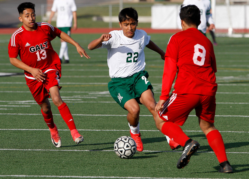 . Alisal High School\'s Joel Garcia (22) splits Galt High School defenders Ramiro Ramirez (13) and Orlando Villalobos (8) during their CIF Nor Cal soccer match in Salinas on Tuesday, March 6, 2018.  Alisal High beat Galt High 3-2 to advance to the Nor Cal semifinals.  (Vern Fisher - Monterey Herald)