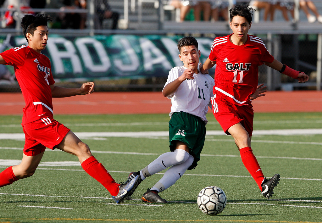 . Galt High School defenders Nathan Villalobos (4) and Alexis Gonzalez (11) battle Alisal High School\'s Jose Trejo (11) during their CIF Nor Cal soccer match in Salinas on Tuesday, March 6, 2018.  Alisal High beat Galt High 3-2 to advance to the Nor Cal semifinals.  (Vern Fisher - Monterey Herald)
