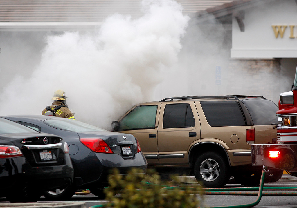 . A Monterey fire fighter works a car fire in the parking lot of Del Monte Center in Monterey on Wednesday, March 7, 2018.  (Vern Fisher - Monterey Herald)