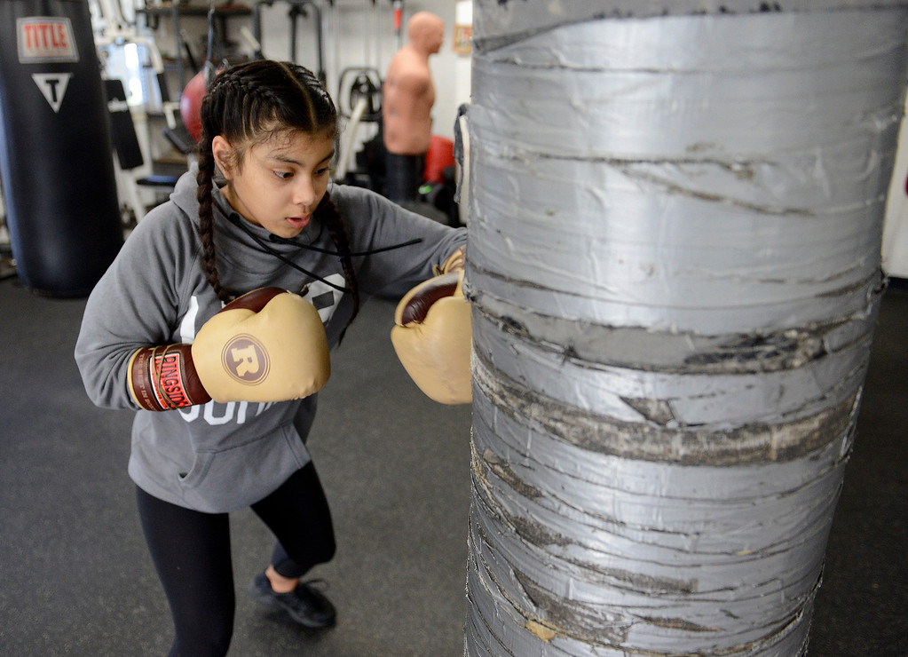 . Salinas Boxing Club fighter Maria Jardines, 14, hits the heavy bag during training at the Salinas Boxing Club on Thursday, March 22, 2018.  (Vern Fisher - Monterey Herald)