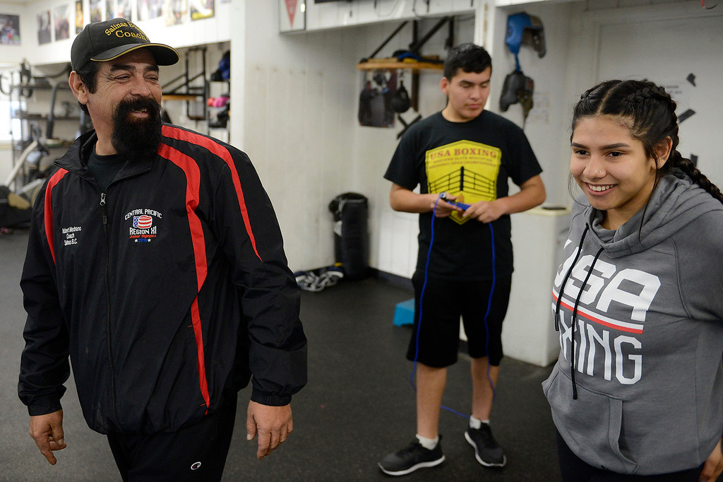 . Boxing coach Robert Medrano with fighters Jose Picazo, 12, and Iris Rivera, 17, at the Salinas Boxing Club on Thursday, March 22, 2018.  (Vern Fisher - Monterey Herald)