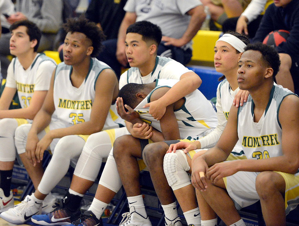 . Monterey\'s Eldrin Arelis embraces an emotional Austin White, who covered his head in his shirt as the final seconds wind down during their win against Saratoga\'s during the CCS Division III boys basketball finals at Santa Clara High School on Saturday March 4, 2017. White tore his ACL in the fall but was able to rehab and play. (David Royal - Monterey Herald)