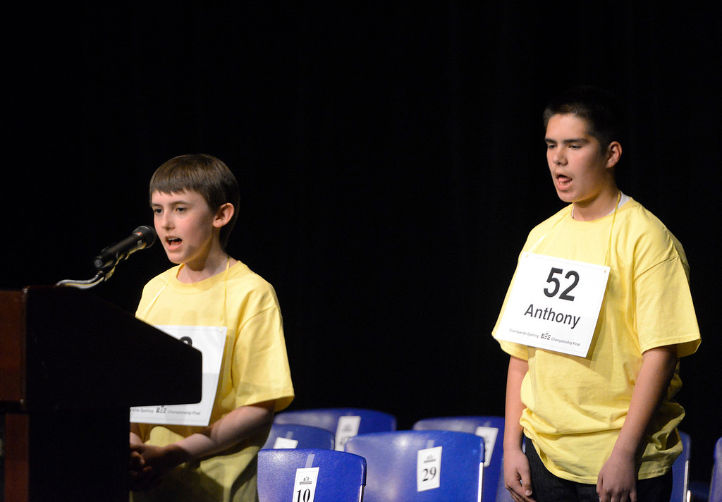 . Countywide Spelling Bee winner Paul Hamrick, left, spells a word for the judges while second place finisher Anthony Santa Ana mouths out the word behind him while waiting for his turn at Hartnell College on Sunday March 5, 2017. Hamrick\'s winning word reparations. He is a seventh grader at Lambert Hamrick Homeschool. Santa Ana is an eighth grader at Washington Middle School.  (David Royal - Monterey Herald)