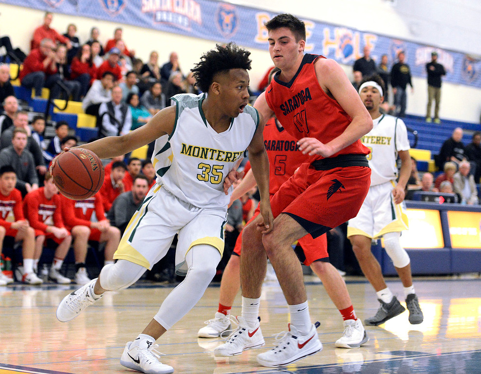 . Monterey\'s Mohanid Adam dribbles around Saratoga\'s Joel Scheidmiller during the CCS Division III boys basketball finals at Santa Clara High School on Saturday March 4, 2017. (David Royal - Monterey Herald)