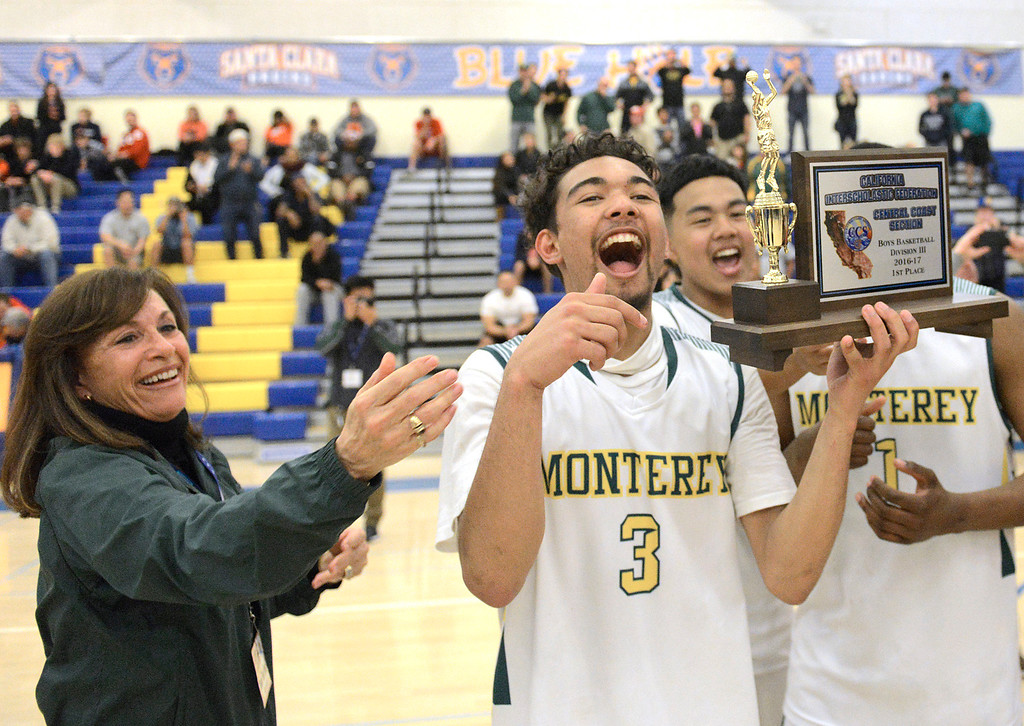 . Monterey High principal Marcie Plummer, left, hands Kobe Ordonio and teammates the trophy after their win against Saratoga during the CCS Division III boys basketball finals at Santa Clara High School on Saturday March 4, 2017. (David Royal - Monterey Herald)
