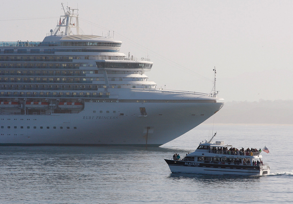 . The whale watching boat Black Fin motors past the cruise ship Ruby Princess at anchor outside the Monterey Harbor on Tuesday, April 3, 2018.  (Vern Fisher - Monterey Herald)