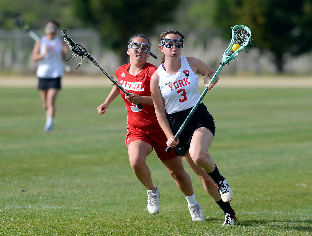 . York\'s Betsy Sugar runs the ball against Carmel\'s Kaley Kinoshita during lacrosse at York School in Monterey on Wednesday April 5, 2017. (David Royal - Monterey Herald)