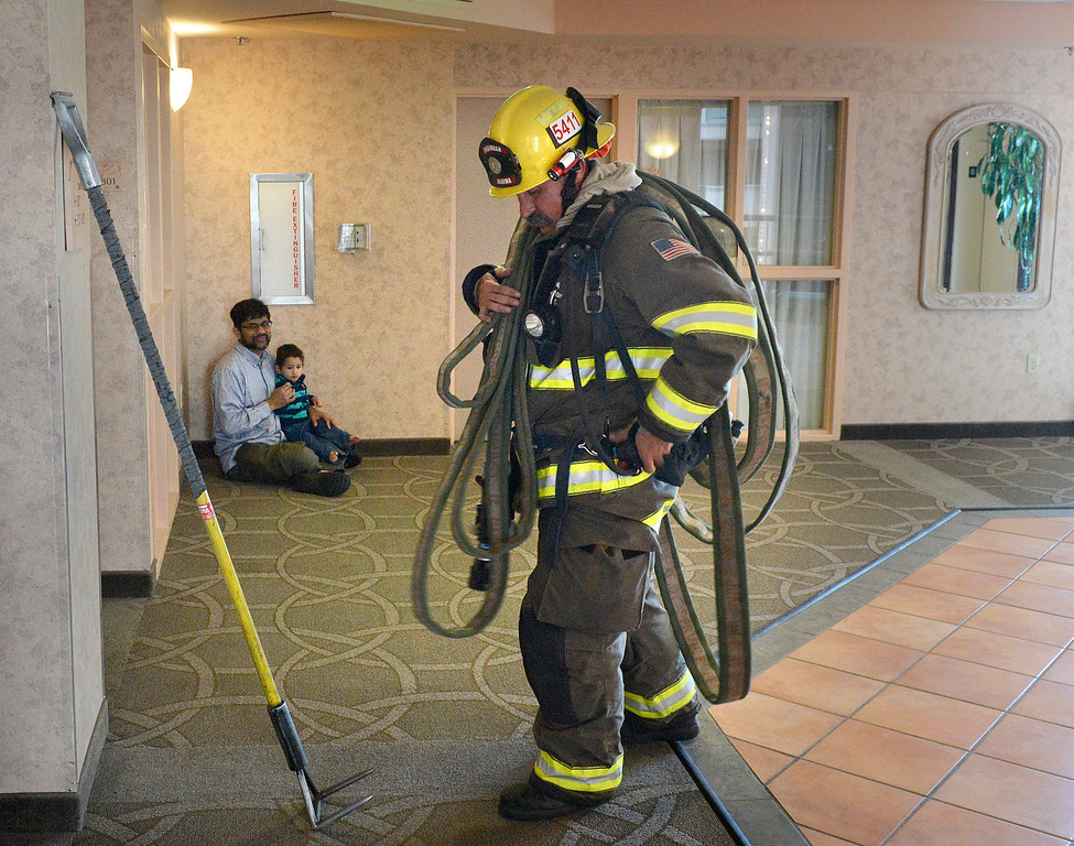 . Kahlid Islam and his son Rayaan, 19 months, watch as Marina Fire engineer Anthony Prado carries a hose on his shoulder during a high rise fire training exercise at Embassy Suites in Seaside on Sunday April 2, 2017. The event, which was hosted by Seaside Fire, was attended by fire units from Monterey, marina, Calfire, North County, AMR and Monterey County Regional Fire. Islam was staying with his family in a room nearby. (David Royal - Monterey Herald)