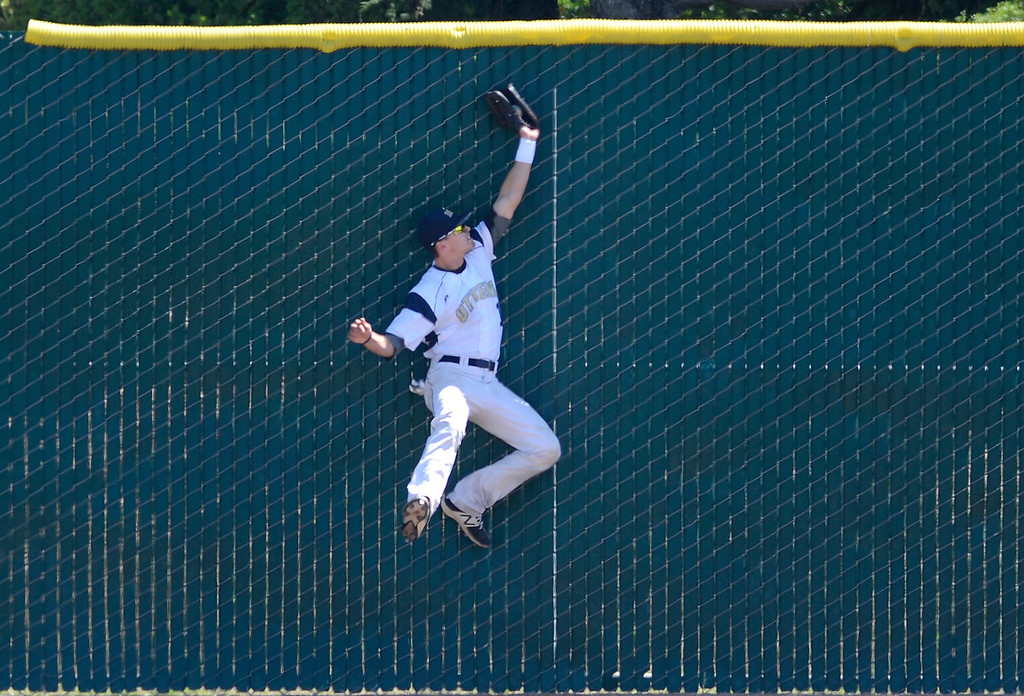 . CSU Monterey Bay\'s Max Sanderson slams into the right field wall after reeling in a fly ball to end the sixth inning during baseball against Cal Poly Pomona at CSUMB in Seaside on Saturday April 1, 2017. The Otters won the game 3-1. (David Royal - Monterey Herald)