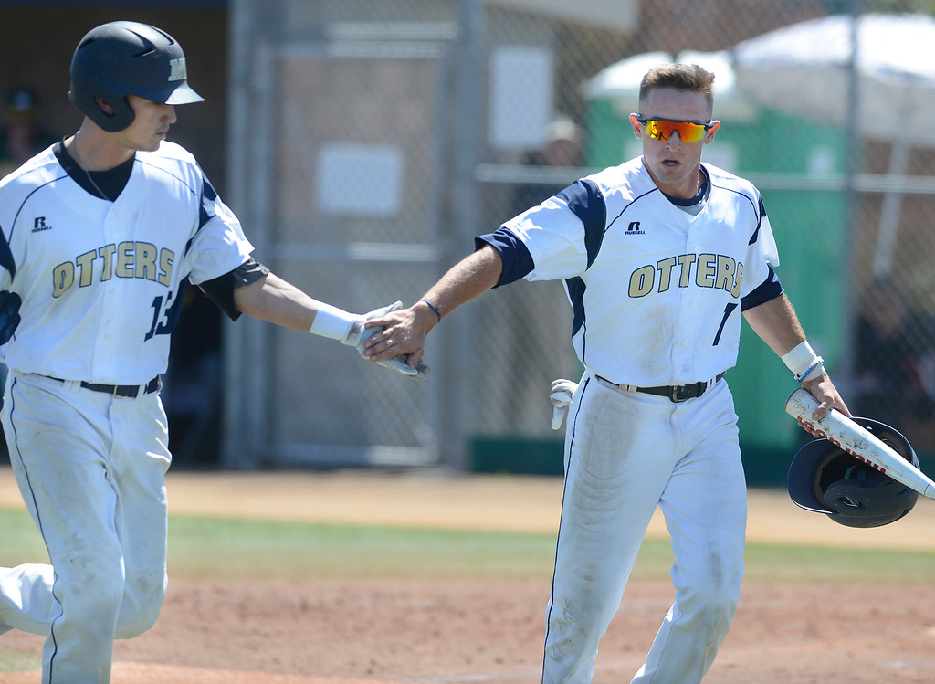. CSU Monterey Bay\'s Zakry Taylor, right, greets teammate Max Sanderson near home plate after Sanderson drove him to home on a sacrifice fly against Cal Poly Pomona\'s Bryce Graddy during baseball at CSUMB in Seaside on Saturday April 1, 2017. The Otters won the game 3-1. (David Royal - Monterey Herald)
