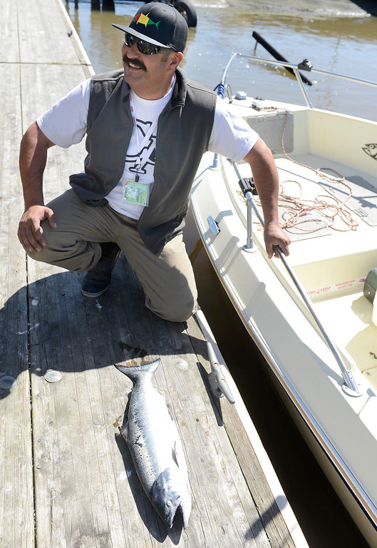 . Manuel Madrigal kneels beside the single salmon that was caught on the boat he was on after returning to the Moss Landing Harbor during the opening day of the recreational salmon season on Saturday April 1, 2017. (David Royal - Monterey Herald)