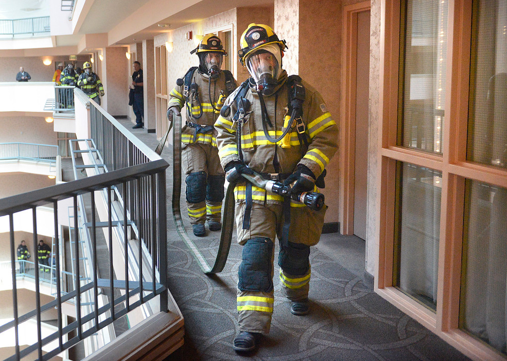. Marina Firefighters carry a fire hose during a high rise fire training exercise at Embassy Suites in Seaside on Sunday April 2, 2017. The event, which was hosted by Seaside Fire, was attended by fire units from Monterey, marina, Calfire, North County, AMR and Monterey County Regional Fire. (David Royal - Monterey Herald)