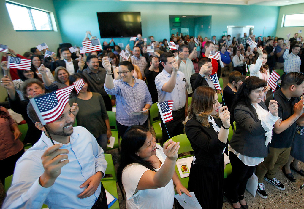 . Approximately one hundred new U.S. citizens wave their American flags after taking the oath during their naturalization ceremony at the Cesar Chavez Library in Salinas on Friday, March 31, 2017.  (Vern Fisher - Monterey Herald)