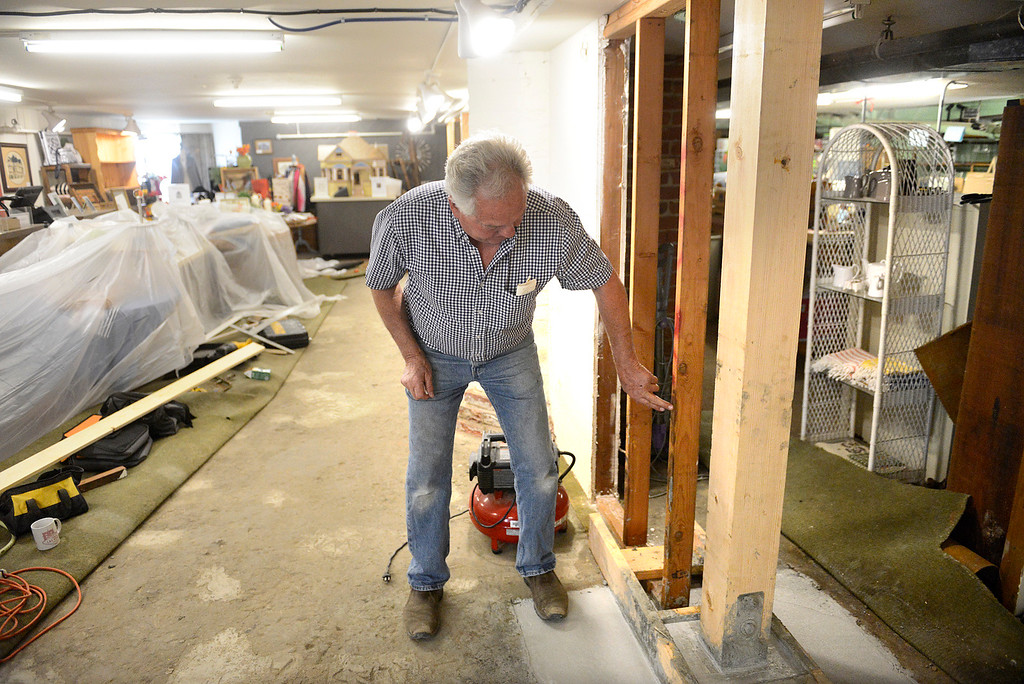 . Steinbeck House volunteer David Bernardi points to new support beams and concrete footings while making repairs inside the Best Cellar gift shop at the historic building in Salinas on Wednesday April 5, 2017. Original brick footings and the support beams above them from when the house was built in 1898 were found to be deteriorating along with some drywall. (David Royal - Monterey Herald)