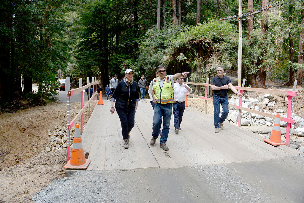 . Monterey County Public Works construction/management specialist Juan Mesa, in yellow, leads Monterey County Supervisors Mary Adams, Luis Alejo and assistant county administrative officer Nick Chiulos, right, along with Cal OES deputy director David Fukutomi and other county officials and representatives across a temporary bridge over Rocky Creek on Palo Colorado Road during a tour of storm damaged areas in Palo Colorado Canyon in Big Sur on Tuesday April 4, 2017. The area of the road sustained major damage after a culvert jammed, (David Royal - Monterey Herald)