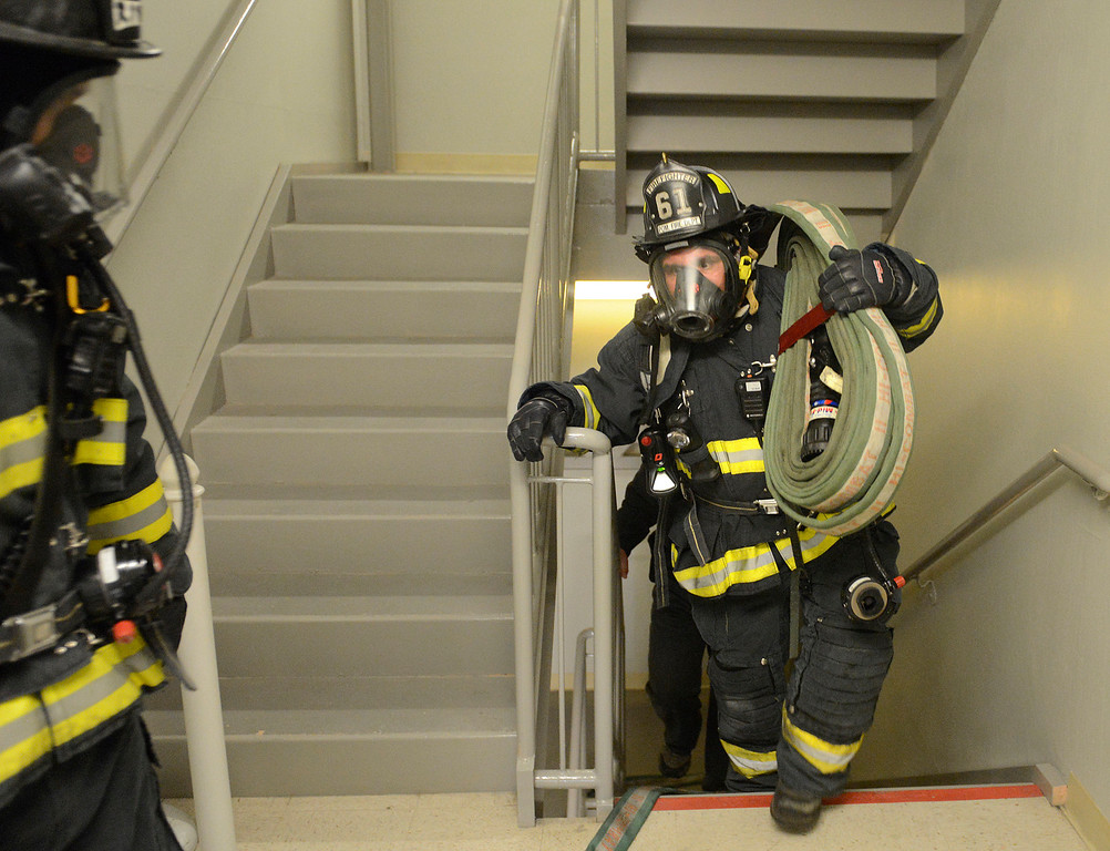 . Presidio of Monterey firefighter Dave Serna lugs a fire hose up to the fourth floor during a high rise fire training exercise at Embassy Suites in Seaside on Sunday April 2, 2017. The event, which was hosted by Seaside Fire, was attended by fire units from Monterey, marina, Calfire, North County, AMR and Monterey County Regional Fire. (David Royal - Monterey Herald)