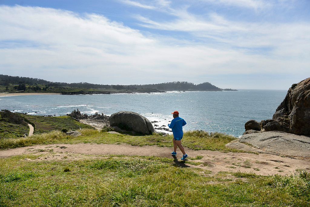 . Refugio Vizcaya of Seaside runs on a trail in Carmel Meadows on as Point Lobos loom sin the background on Tuesday April 4, 2017. (David Royal - Monterey Herald)