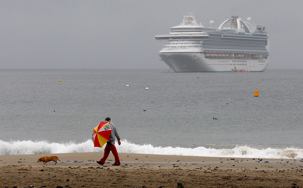 . A man walks on Del Monte State Beach in Monterey during a rain shower on Tuesday, March 13, 2018.  (Vern Fisher - Monterey Herald)