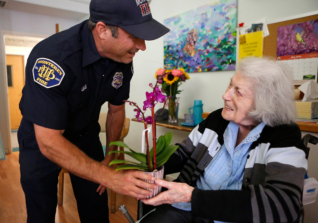 . Monterey Fire engineer Jaason Lease delivers Mother\'s Day flowers to Ella Jeffries. 97, at the Carmel Hills Care Center as part of the I Remember Mama event in Monterey on Sunday May 13, 2018. (David Royal/ Herald Correspondent)