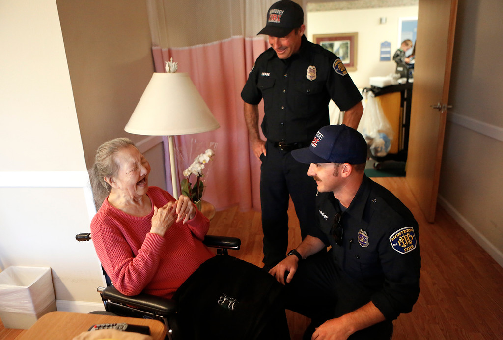 . Hideko Wingrove reacts after Monterey Fire engineer Jaason Lease and firefighter Silas Fischer deliver Mother\'s Day flowers to her at the Carmel Hills Care Center as part of the I Remember Mama event in Monterey on Sunday May 13, 2018. (David Royal/ Herald Correspondent)