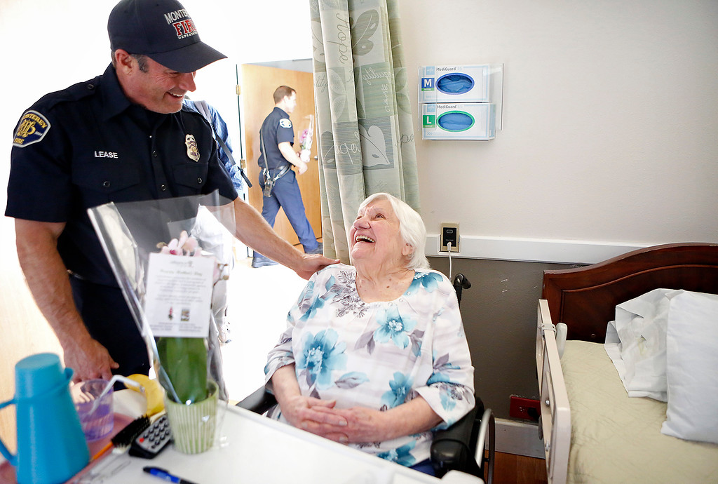 . Monterey Fire engineer Jaason Lease delivers Mother\'s Day flowers to Marie Calabretta at the Carmel Hills Care Center as part of the I Remember Mama event in Monterey on Sunday May 13, 2018. (David Royal/ Herald Correspondent)