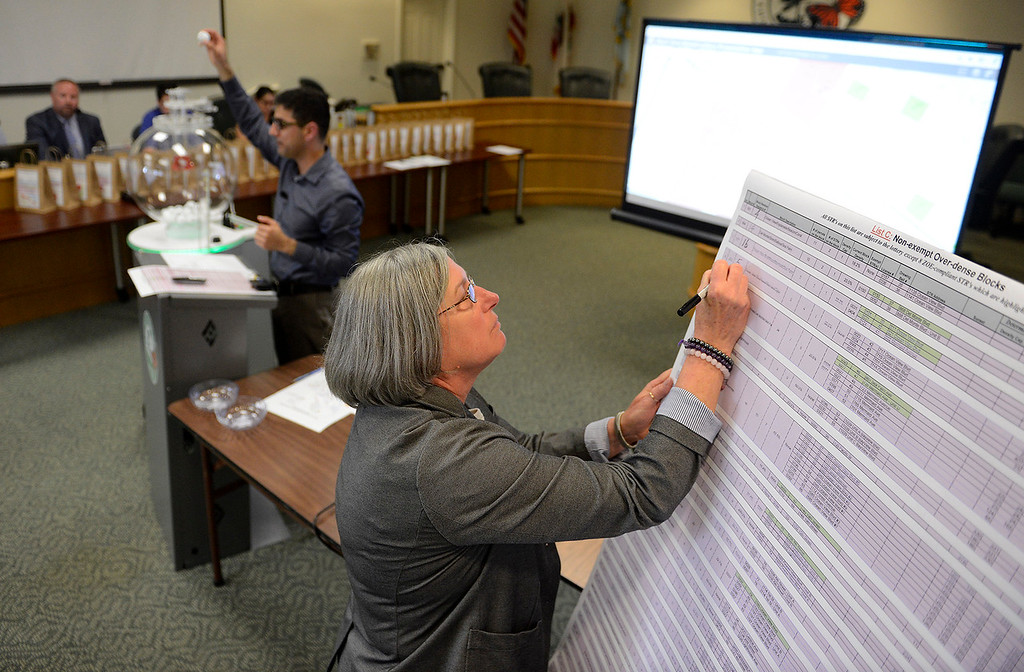 . Pacific Grove city employees Haroon Noori and Terri Schaeffer work a special meeting on Tuesday, May 22, 2018 during a lottery to determine restrictions on short-term rental properties.  (Vern Fisher - Monterey Herald)