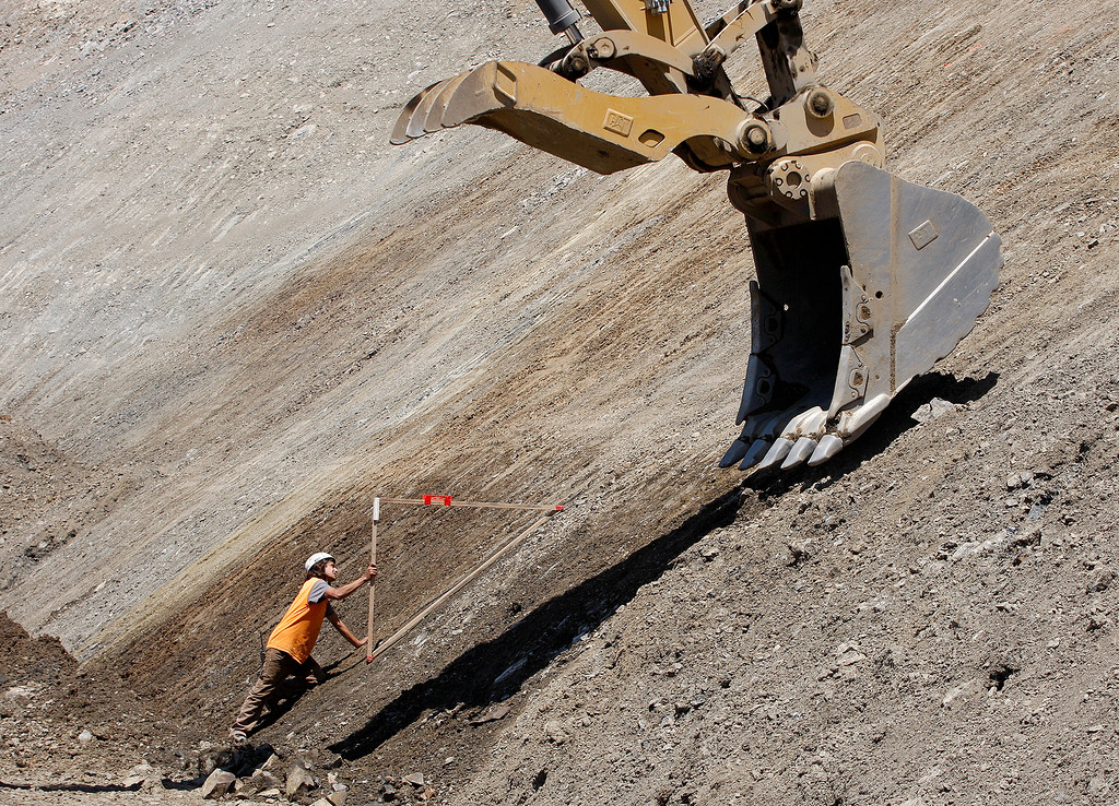 . Jesse Foster uses a forty-five degree form to monitor the work being done by a heavy machine operator as work continues at the Mud Creek slide on Highway One south of Big Sur on Monday, May 7, 2018.  (Vern Fisher - Monterey Herald)