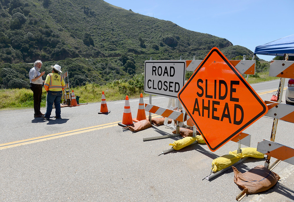. Arlene Guzzie of Cal Trans informs motorists traveling north near Salmon Creek of the Highway One road closure due to the Mud Creek slide on Monday, May 7, 2018.  (Vern Fisher - Monterey Herald)