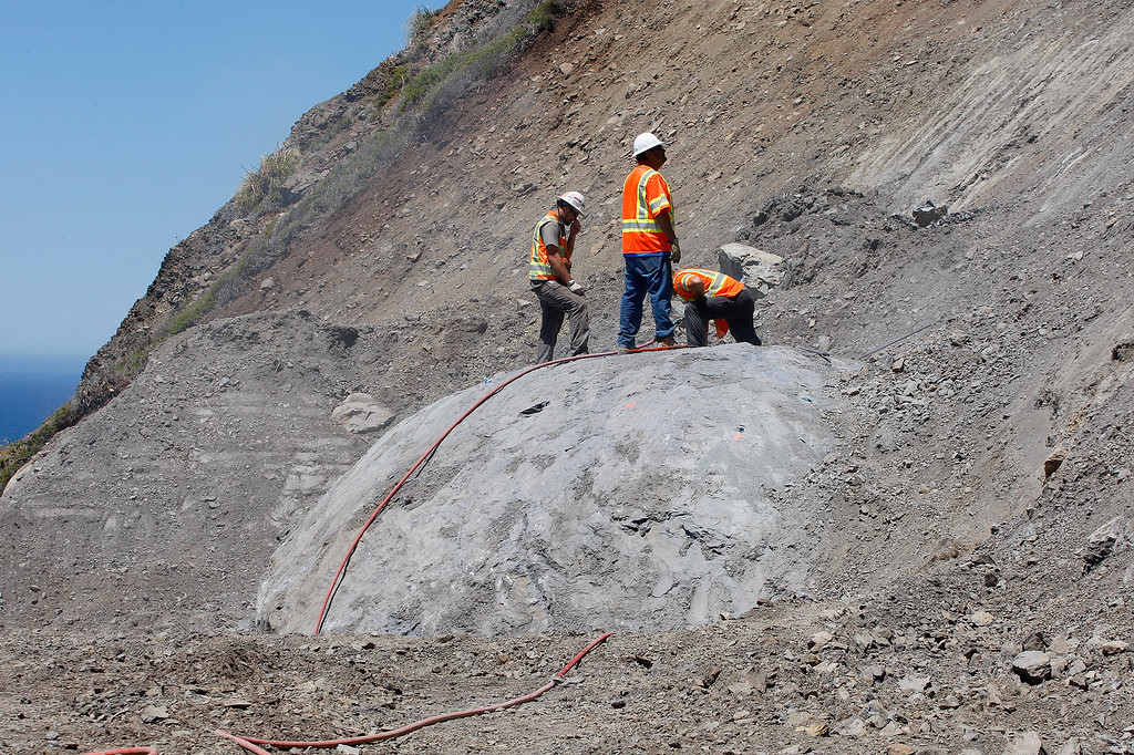 . Cal Trans crew prepare to blast a problem boulder upslope of the Highway One roadway at the Mud Creek slide south of Big Sur on Monday, May 7, 2018.  (Vern Fisher - Monterey Herald)