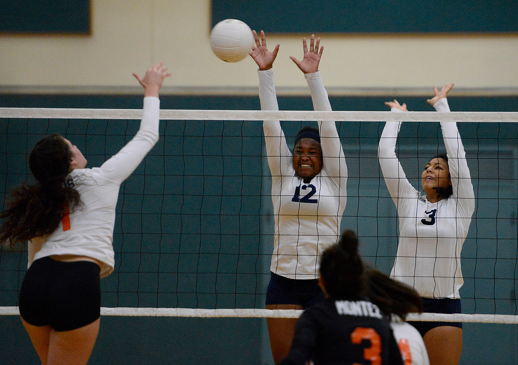 . Woodland\'s Zoe Wais (1) has her shot blocked by Santa Catalina\'s Maria Santos (12) and Kia Shoemaker (3) during their CIF State Girls Volleyball Championships - Division III at Santa Catalina School in Monterey on Wednesday, Nov. 15, 2017.  (Vern Fisher - Monterey Herald)
