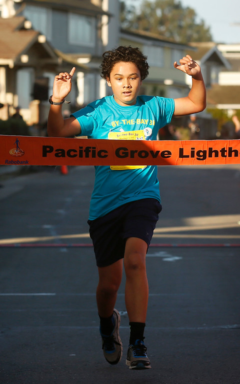. Adam Galinato, 11, raises his arms as he crosses the finish line to win the By the Bay 3K kids fun run at Lovers Point in Pacific Grove on Saturday November 11, 2017. (David Royal/Herald Correspondent)