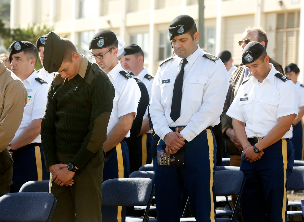. Marine P.F.C. Jesse Pedersen, left, and other soldiers bow their heads during the invocation during the Veterans Day Wreath Laying Ceremony at the Berlin Wall Memorial at the Defense Language Institute in Monterey on Thursday November 9, 2017. (David Royal/Herald Correspondent)