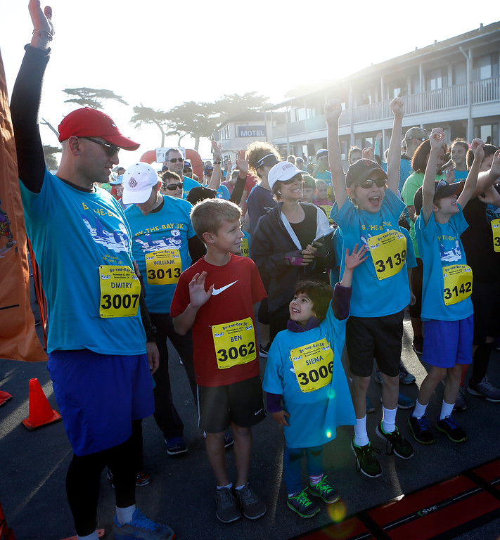 . Runners raise their arms after being asked if this was their first race before the start of the during the By the Bay 3K kids fun run at Lovers Point in Pacific Grove on Saturday November 11, 2017. (David Royal/Herald Correspondent)