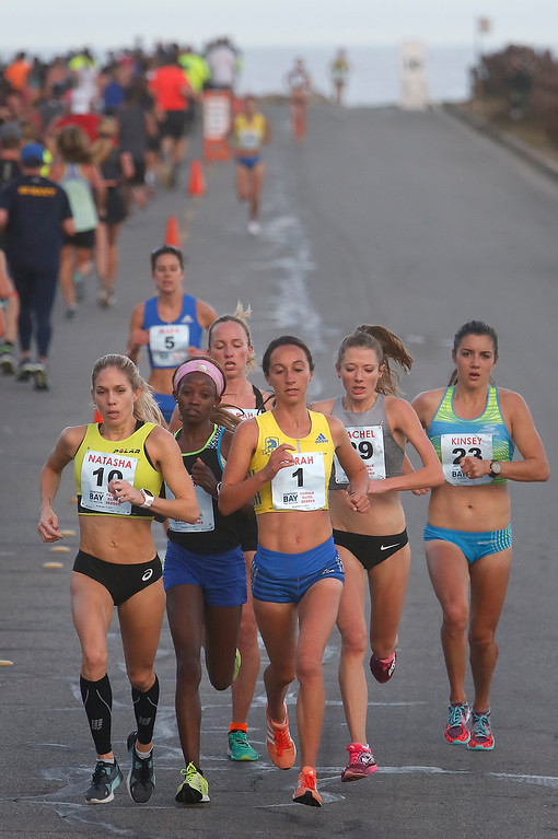 . Monicah Ngige, second from left, of Kenya makes her move into the lead on Oceanview Boulevard in Pacific Grove, Calif. on her way to winning the Monterey Bay Half Marathon on Sunday November 12, 2017. (David Royal/Herald Correspondent)