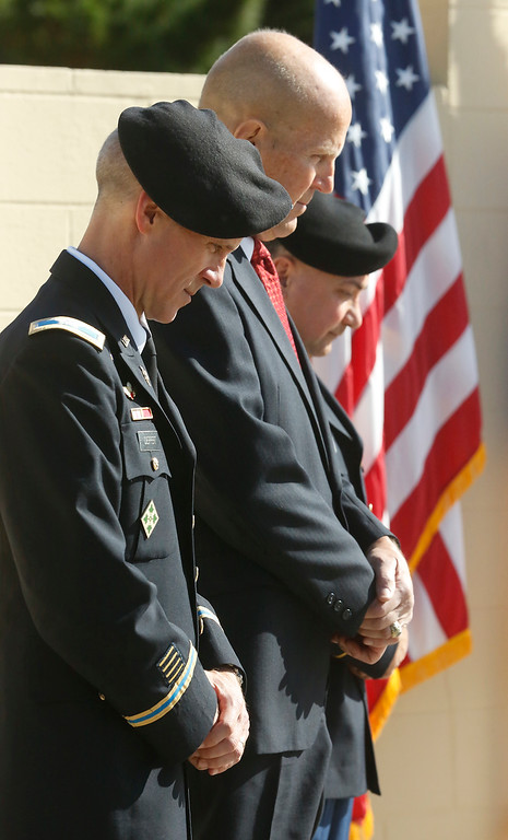 . Defense Language Institute Commandant Col. Phil Deppert, left, Del Rey Oaks mayor Jerry Eden, and DLI Command SGT. Ryan Ramsey bow their heads during the invocation during the Veterans Day Wreath Laying Ceremony at the Berlin Wall Memorial at the DLI in Monterey on Thursday November 9, 2017. Eden who retired as Lt. Col. From the Army is a veteran of the Berlin Brigade. (David Royal/Herald Correspondent)