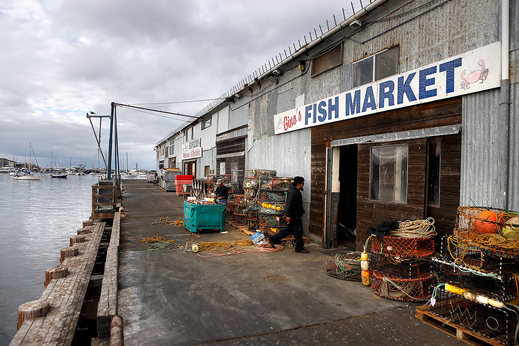 . Giovanni Nevoloso prepares crab traps for the upcoming commercial Dungeness crab season as Giovanni Sanchez of Royal Seafood walks by outside Nevoloso\'s business, Gino\'s Fish Market on Wharf No. 2 in Monterey on Wednesday November 8, 2017. Nevoloso owner the Gabbiano fishing boat and said he has been fishing for 60 years.  (David Royal/Herald Correspondent)