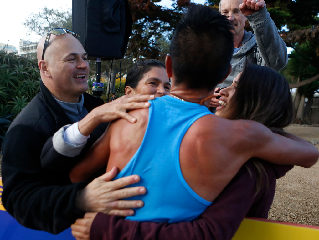 . Daniel Tapia of Prunedale, Calif. embraces family members after winning the Monterey Bay Half Marathon in Monterey, Calif. on Sunday November 12, 2017. (David Royal/Herald Correspondent)