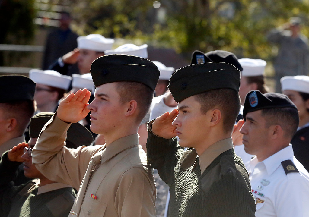 . Marines P.V.T. Robert  Goodwin, left, and Marine P.F.C. Jesse Pedersen salute the American flag during the playing of the National Anthem during the Veterans Day Wreath Laying Ceremony at the Berlin Wall Memorial at the Defense Language Institute in Monterey on Thursday November 9, 2017. (David Royal/Herald Correspondent)