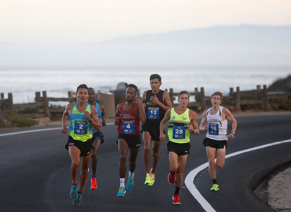 . Daniel Tapia, left, of Prunedale, Calif. runs past Asilomar State Park with the lead men on his way to winning the Monterey Bay Half Marathon in Pacific Grove, Calif. on Sunday November 12, 2017. (David Royal/Herald Correspondent)