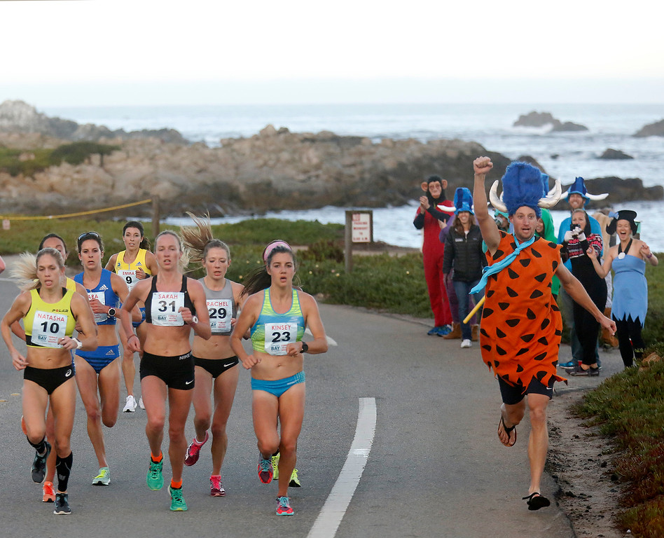 . A man in a Flintstone suit runs beside the lead pack of female runners as they pass Point Pinos during the Monterey Bay Half Marathon in Pacific Grove and Monterey, Calif. on Sunday November 12, 2017. (David Royal/Herald Correspondent)