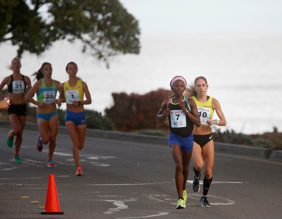 . Monicah Ngige, center left, of Kenya makes her move into the lead on Oceanview Boulevard in Pacific Grove, Calif. on her way to winning the Monterey Bay Half Marathon on Sunday November 12, 2017. (David Royal/Herald Correspondent)