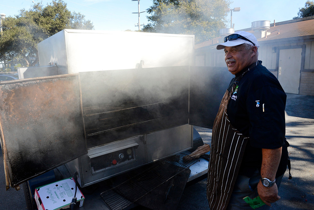 . Jerry Kona of Kona Jerry\'s catering checks on the hams and turkeys in his smoker on Wednesday, November 22, 2017 in preparation for the annual Thanksgiving Day meal at the Monterey County Fairgrounds. (Vern Fisher - Monterey Herald)