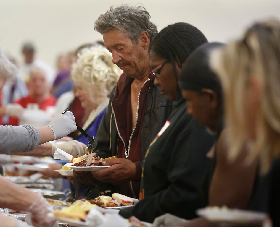 . Harvey Byrum looks on as a volunteer pours gravy on his turkey during the Community Thanksgiving Dinner at the Monterey County Fair and Events Center in Monterey on Thursday November 23, 2017. (David Royal/Herald Correspondent)