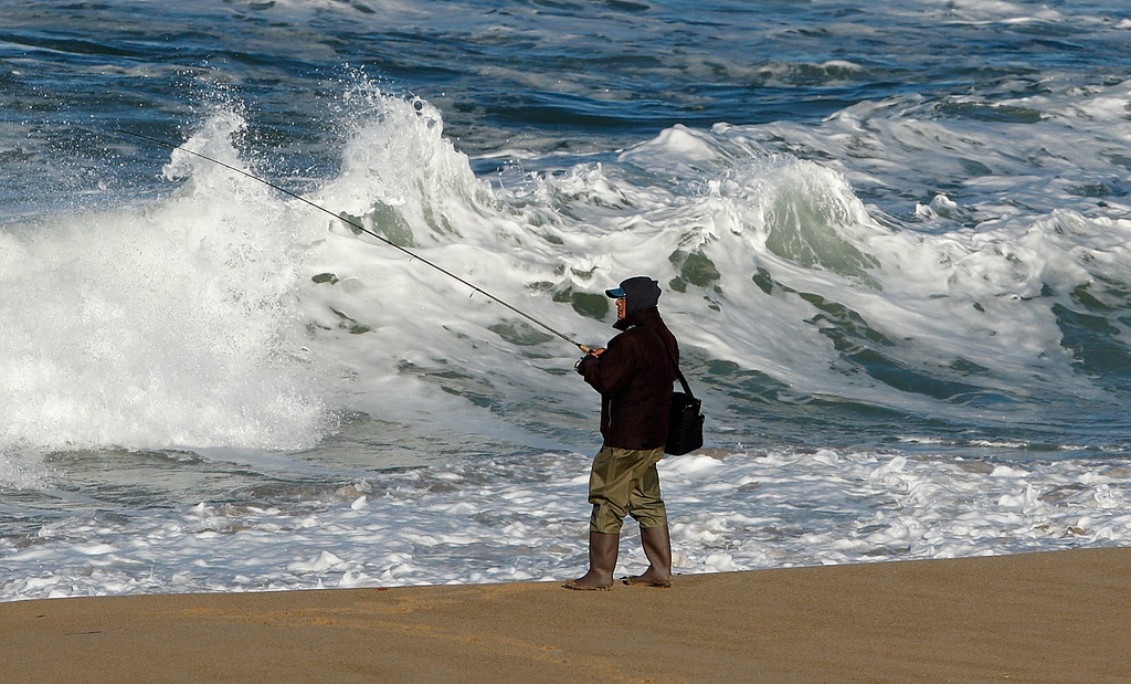 . A surf fisherman deals with the large surf at Marina State Beach on Thursday, Nov. 30, 2017.  (Vern Fisher - Monterey Herald)