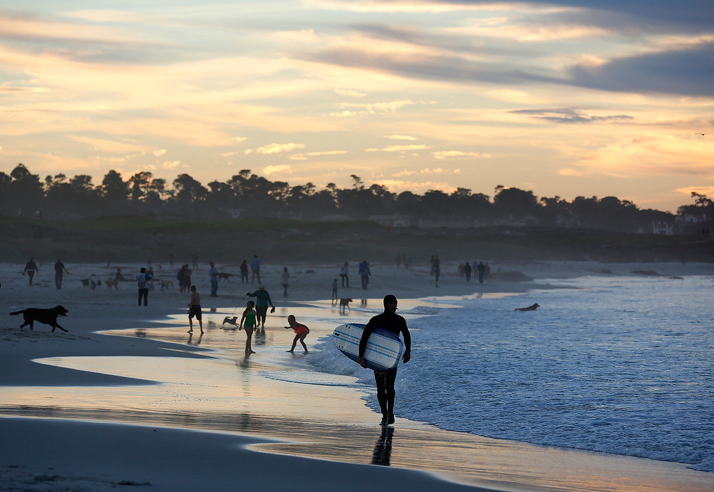 . A surfer, dog walkers and others mingle on Asilomar State Beach as the sun sets in Pacific Grove on Saturday November 25, 2017. (David Royal/Herald Correspondent)