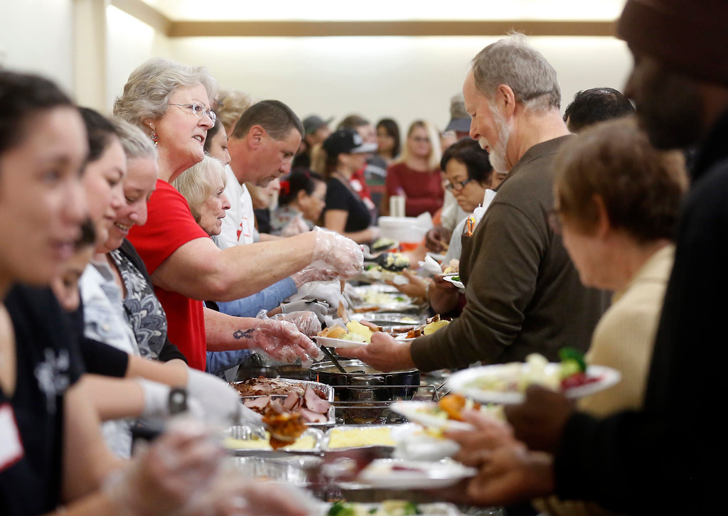 . Volunteer Joan Hyler of Pacific Grove greets diners while serving turkey during the Community Thanksgiving Dinner at the Monterey County Fair and Events Center in Monterey on Thursday November 23, 2017. (David Royal/Herald Correspondent)