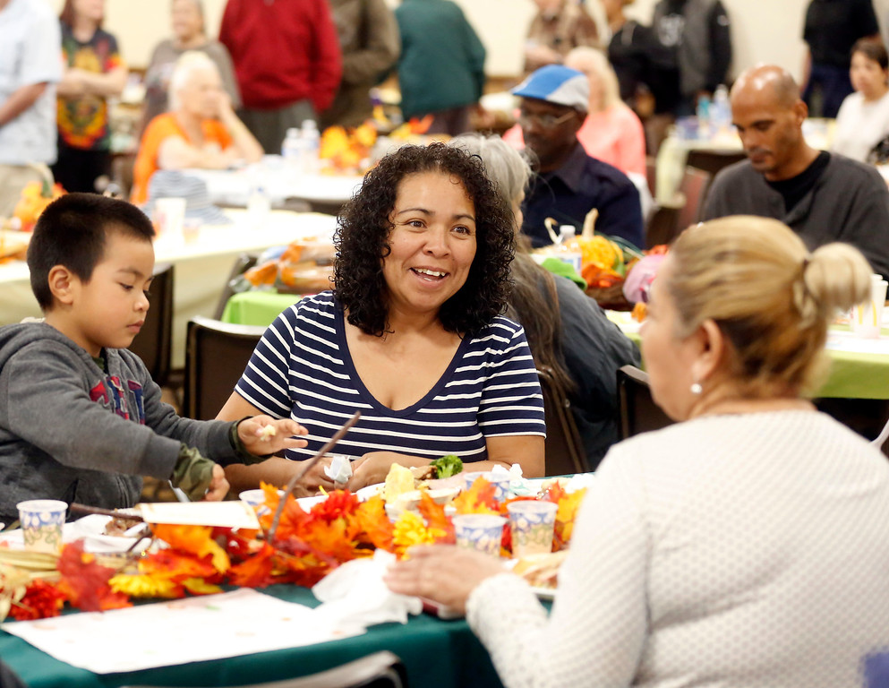 . Vilma Jarquin and her son Josemaria Ortiz, 4, share their meal with friends during the Community Thanksgiving Dinner at the Monterey County Fair and Events Center in Monterey on Thursday November 23, 2017. (David Royal/Herald Correspondent)