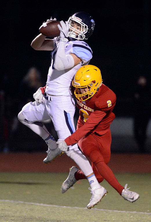. Valley Christian\'s Anthony Flores reels in a pass over Palma\'s Vianni Fratangelo during the CCS Open Division III championship football game at Oak Grove High School in San Jose on Friday November 25, 2016. (David Royal - Monterey Herald)