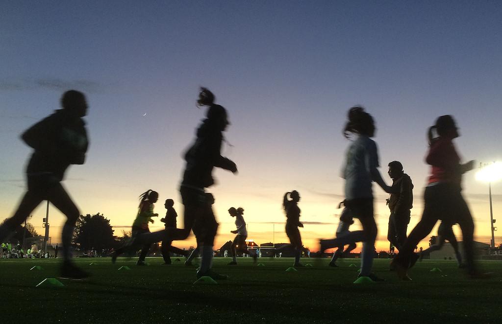 . Alisal girls soccer coach Raymundo Navarro, right, walks through as players warm up before taking the field against North Salinas North Salinas at Alisal High School in Salinas on Thursday December 1, 2016. (David Royal - Monterey Herald)